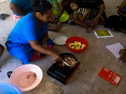 One of our Health Champions demonstrating how to drain the fat out of a canned corn beef. Corn beef is commonly eaten in households in Kiribati